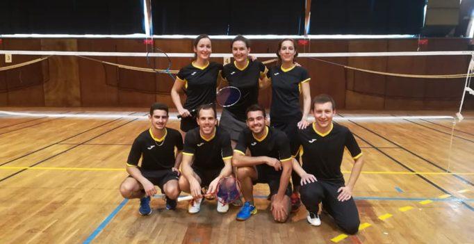 Photos de 7 joueurs de badminton de l'équipe des chartrons sur un terrain de badminton habillés en noir et jaune. Devant 4 hommes accroupis, derrière 3 femmes debout