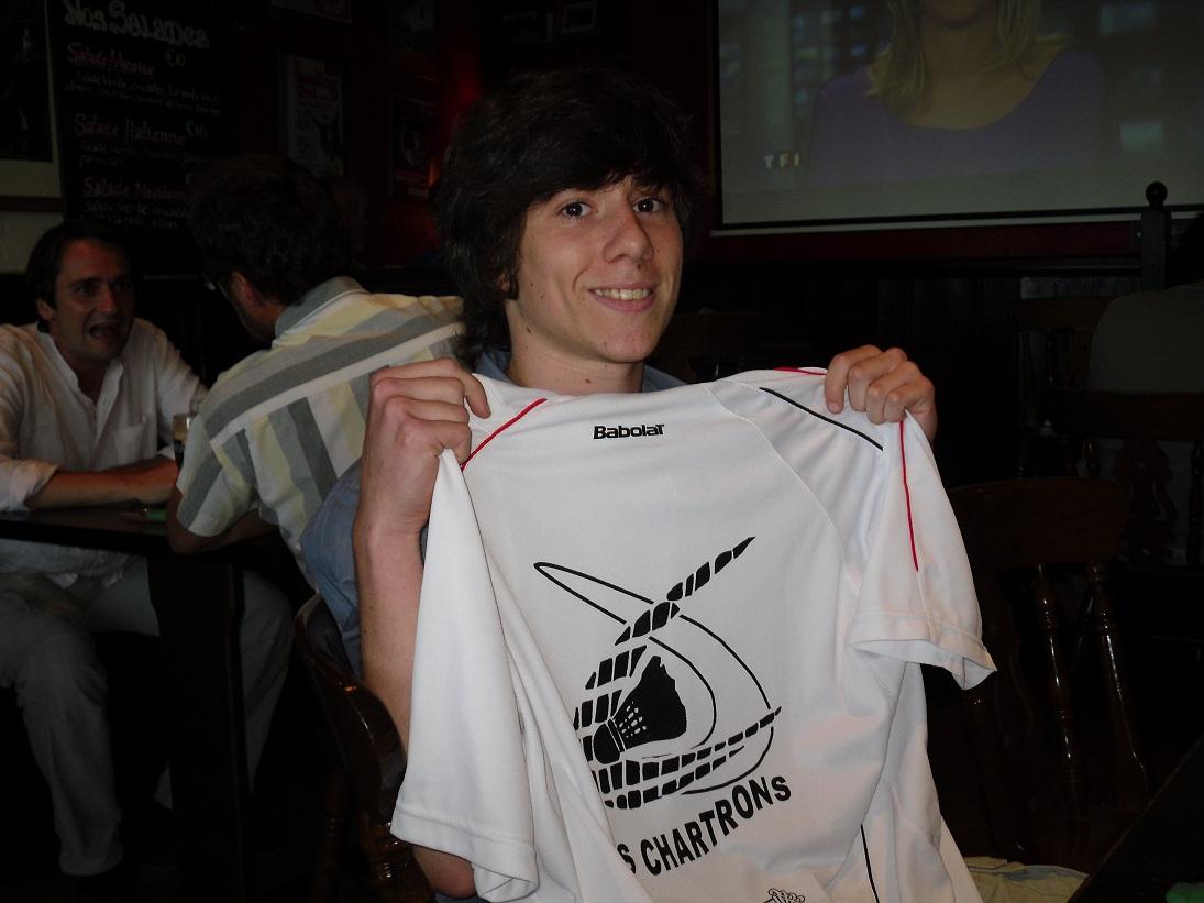 Un jeune homme tenant devant lui un T-shirt blanc avec le logo US chartrons en noir