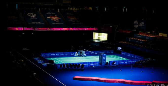 Un terrain de compétition de badminton éclairé dans une salle avec des gradins dans le noir