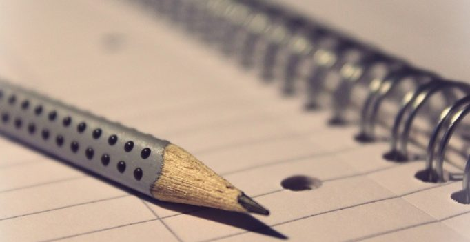 Gros plan du un crayon de papier posé sur un cahier à spirales. Le fond devient flou