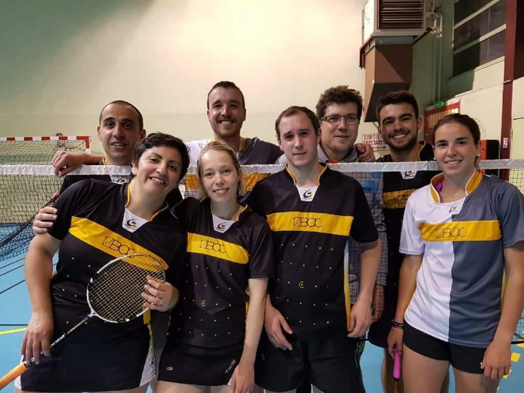 8 joueurs de badminton debout. 4 devant un filet et 4 derrière