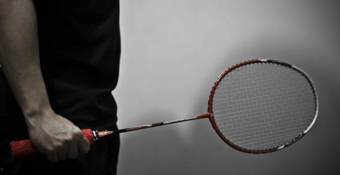 Une photo en noir et blanc en gros plan sur un homme tentant une raquette de badminton. Celle-ci est en couleur rouge