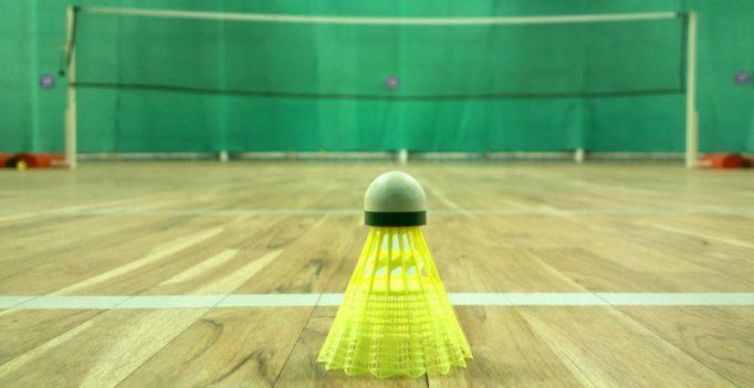 un volant de badminton en plastique jaune fluorescent posé au sol sur un parquet au premier plan. Derrière le terrain de badminton avec le filet
