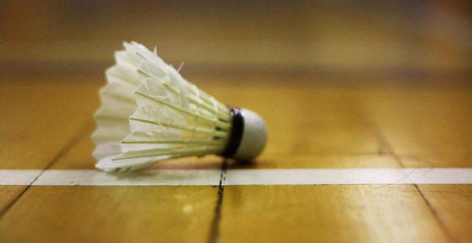 Un volant de badminton posé sur un sol en parquet. Le fond est flou