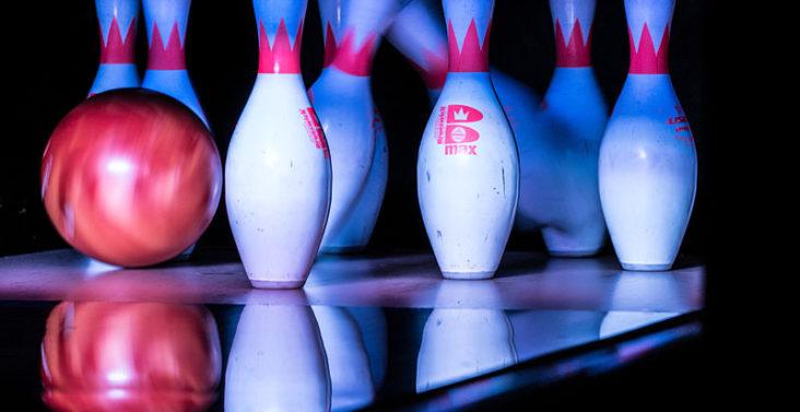 Une boule de bowling rouge qui tape les quilles