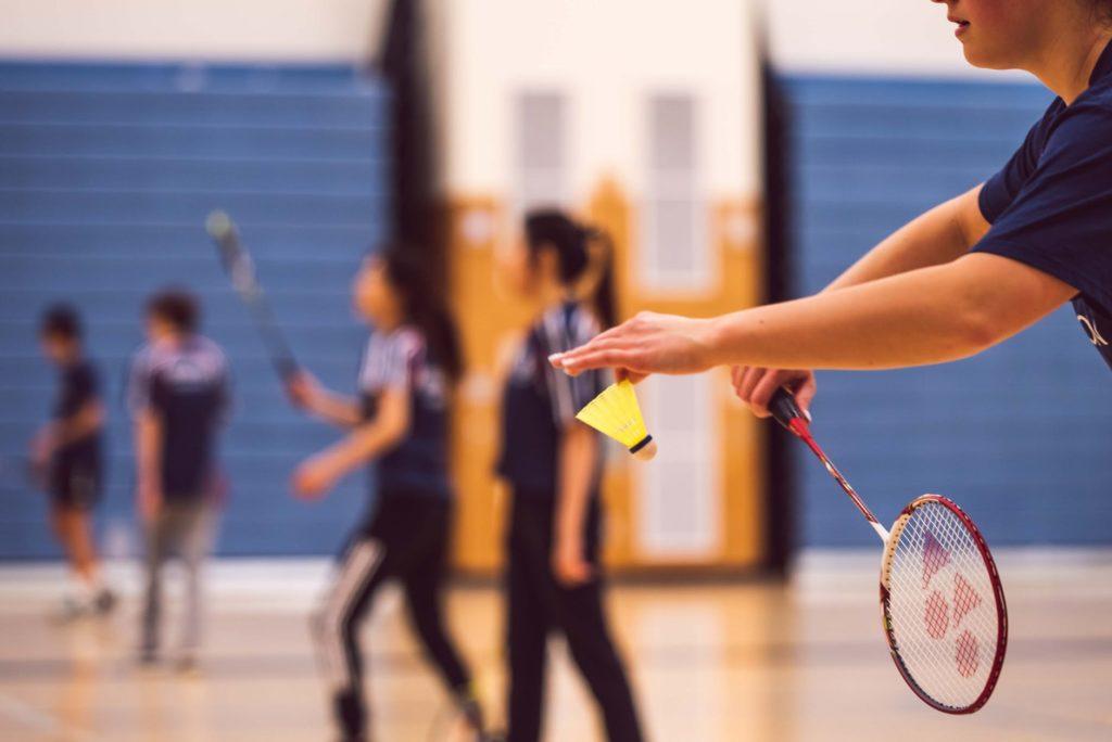 au premier plan un zoom sur un service de badminton. En arrière plan deux joueuses de badminton