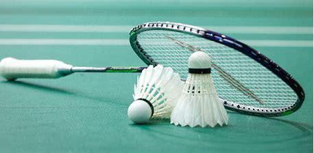 une raquette de badminton posée sur 2 volants au sol